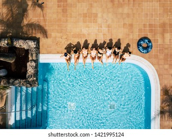 Friends females caucasian people enjoying the swimming pool in summer holiday vacation at hotel or resort - high top vertical view of young women sit down at the poolside in friendship together