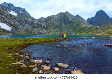 Friends fishing at Vishnusar lake on Kashmir great lakes trek in Sonamarg, India. Rocky terrain and  turquoise lake/tarn with snow mountains and glacier. Amazing nature. Hiking Trekking in Himalayas