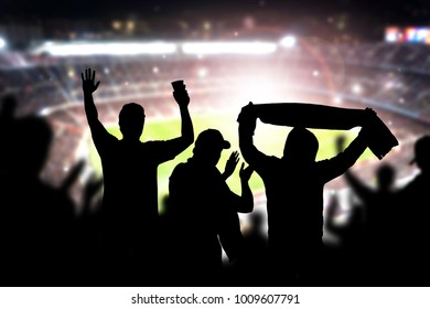 Friends at football game in soccer stadium. Crowd cheering and celebrating a goal in arena during match. Silhouette people in live sport audience having fun.