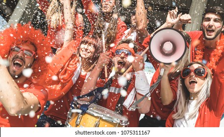 Friends football supporter fans cheering with confetti watching soccer match event at stadium - Young people group with red t-shirts having excited fun on sport world championship concept