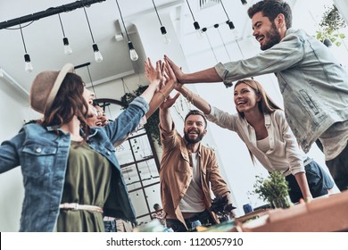 Friends forever! Group of young people giving each other high-five in a symbol of unity and smiling while having a dinner party