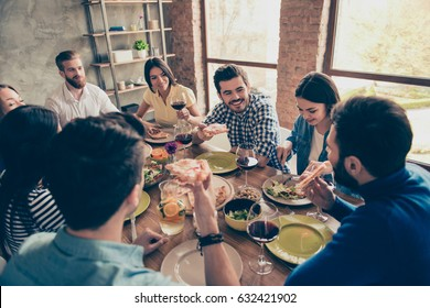 Friends forever! Multiethnic group of young cheerful people are having fun at home on the party with tasty food, drinks, jokes