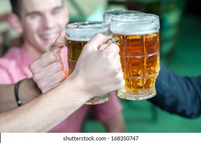 Friends with a fresh beer in a Beer pub. close-up on beer stein