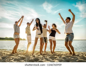 Friends funny dance on the beach under sunset sunlight. Sunny day and friendship.