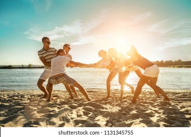 Friends funny tug of war on the beach under sunset sunlight in summer sunny day.
