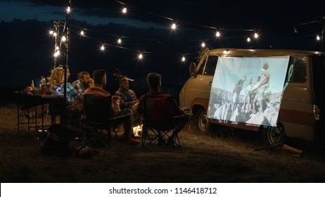 Friends gathering in campsite around bonfire and watching movie with projector on van side in dark evening