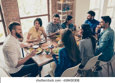 Friend`s gathering for feast. Cheerful youth is having tasty food and wine at the indoor party. So many emotions and memories to share!