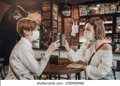 Friends girls in a cafe and communicating with each other. Drink coffee and wear medical protective masks. An outbreak of the coronavirus epidemic. New rules for social distance and isolation