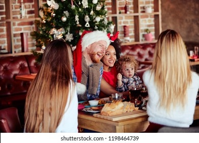 Friends giving gift to toddler while sitting at table. Christmas tree in background. Christmas holiday concept.