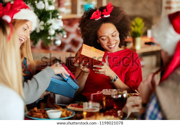 Friends giving gifts to each other while sitting at table. In background Christmas tree. Christmas holidays concept.