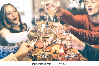 Friends group celebrating Christmas toasting champagne wine at home dinner - Winter holiday concept with young people enjoying time and having fun together - Azure vintage filter with focus on glasses