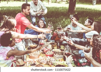 friends. group of happy young people on picnic sitting on lawn drinking wine laughing and celebrating. diversity and friendship concept.