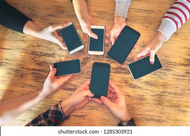 Friends group having fun together using smartphones - Hands detail sharing content on social network with mobile smart phone -Technology concept with people millennials online addicted with cellphone