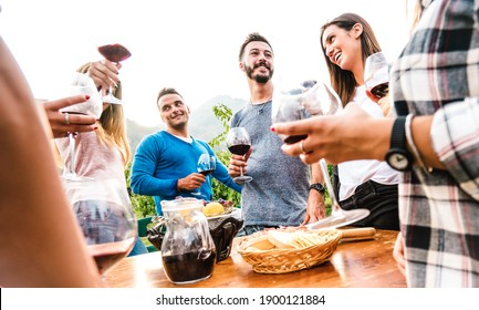 Friends group having fun together at garden party - Young people enjoying harvest time drinking red wine at farm house vineyard - Friendship concept with men and women outside on warm sunset filter