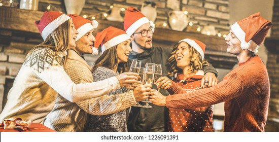 Friends group with santa hats celebrating Christmas with champagne wine toast at home dinner - Winter holidays concept with young people enjoying time and having fun together - Focus on glasses