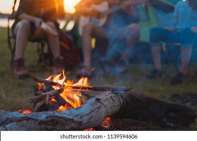 Friends group travel summer camping fire together in forest with backpack and tent picnic drinks beer,water at nature outdoor young teenager talking relax,rest near mountain view sunset.