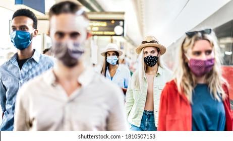 Gruppe der Freunde, die am Bahnhof spazieren geht - Neues normales Reisekonzept mit jungen Menschen, die von Schutzmaske bedeckt sind - Fokus auf blondes Mädchen mit Hut