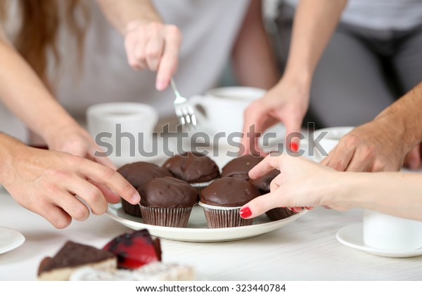 Mains d'amis avec desserts et tasses de thé, gros plan