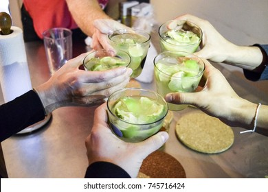 Friends hands holding Brazilian caipirinha drinks saying cheers