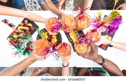 "Friends hands toasting "" Sex on the Beach "" fancy drinks - Young people having fun together drinking cocktails at happy hour with fruit snacks buffet - Summer party time concept on bright vivid filter"