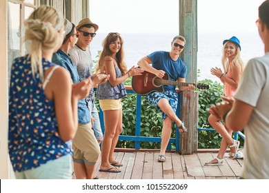 Friends hanging out on vacation at an old wooden cabin porch by the sea while macho man is playing guitar and others are giving him a round of applause and appreciation.