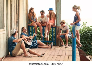 Friends hanging out on vacation at an old wooden cabin porch by the sea while one of them is playing guitar and others are listening