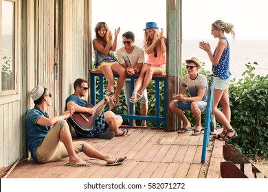 Friends hanging out on vacation at an old wooden cabin porch by the sea while one of them is playing guitar and others are giving him a round of applause