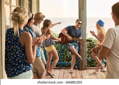 Friends hanging out on vacation at an old wooden cabin porch by the sea while macho man is playing guitar and others are giving him a round of applause and appreciation