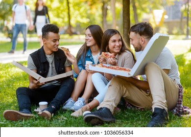 Friends hanging out in park, talking and eating pizza out of box. Beautiful young people on a picnic.