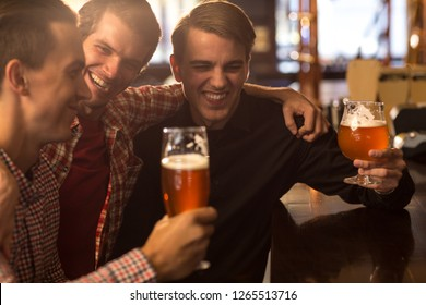 Friends hanging out together in bar. Cheerful and happy facial expressions of man laughing, having fun, communicating in bar. Men holding glasses of fresh, delicious beer.