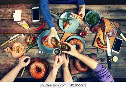 Friends Happiness Enjoying Dinning Eating Concept. Happy meeting friends. Enjoying dinner with friends. Top view of group of people having dinner together while sitting at the rustic wooden table.