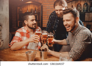 friends are happy and funny men with glasses of beer clink bar.