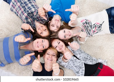friends happy group in circle together on floor, showing thumbs up