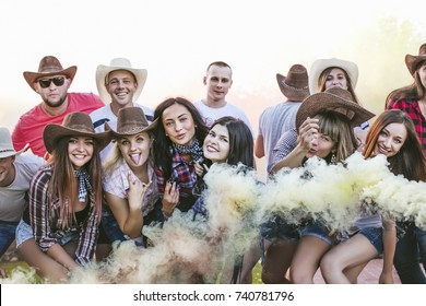 Friends happy at the party funny young together with smiles and crackers with colored smoke
