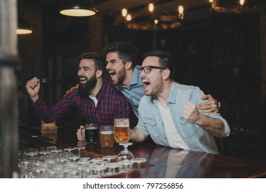 Friends are happy while watching game at te ub and drinking beer.