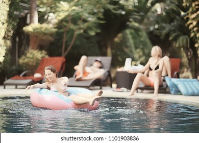friends have fun in the summer pool at the hotel / cheerful company of young friends of men and women in summer swim in the pool on vacation hotel