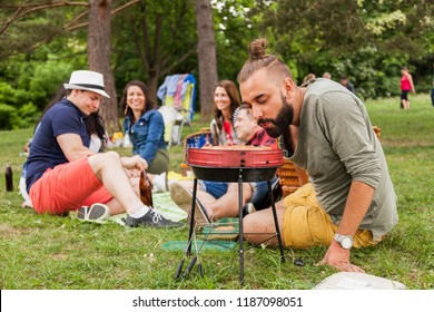 friends have picnic in the park enjoy carefree lifestyle. hipster prepares grilled meat. students gathering concept