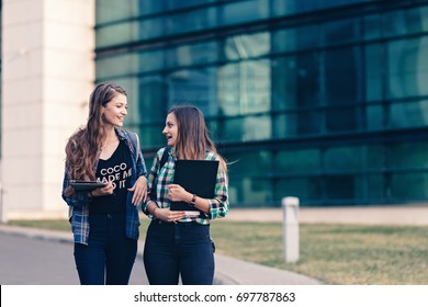 Friends having adorable blonde hair leaving the school after class. Still in serious discussion, may be about their academics. Girls are looking studious, but trendy at the same time. Back to school