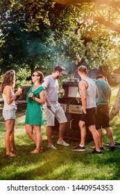Friends having a barbecue grill party with drinks, food and cooking outdoor. Camping concept with friends and people