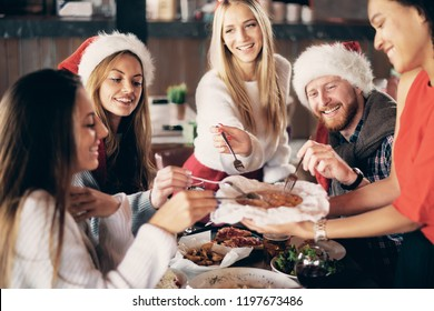 Friends having dinner at home at Christmas eve. Winter hoidays concept.