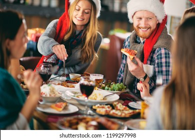 Friends having dinner at home at Christmas eve. Winter holidays concept.