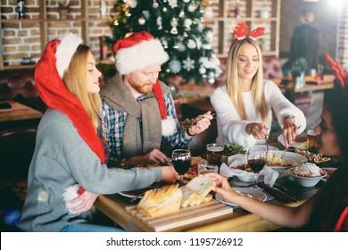 Friends having dinner on Christmas` eve at restaurant. Christmas holidays concept.