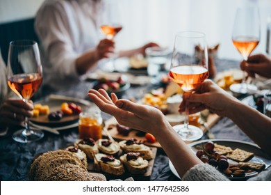 Friends having a dinner party with different kinds of appetizers and rose wine.
