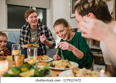 Friends are having a dinner party at home. They are laughing while eating spaghetti carbonara.