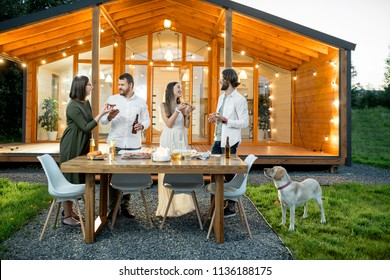 Friends having a dinner with pizza on the backyard of the modern house decorated with lights during the evening time outdoors