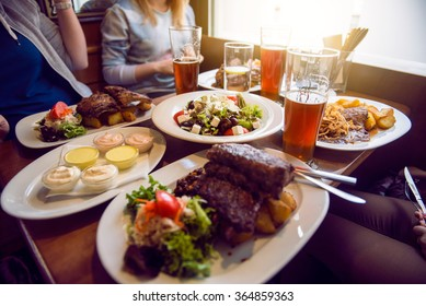 Friends having a dinner in the restaurant with salad, barbeque and beer