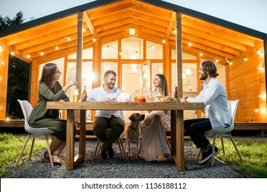 Friends having a dinner sitting at the table on the backyard of the modern house decorated with lights during the evening time outdoors