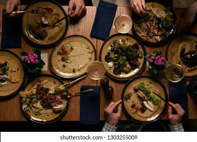 Friends having dinner. Top view of people having dinner together while sitting at wooden table