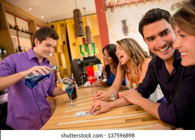 Friends having drinks at the bar looking very happy