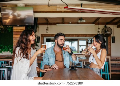 Friends having a drinks in a cozy house. They are sitting at a wooden table. They are joining their beers.